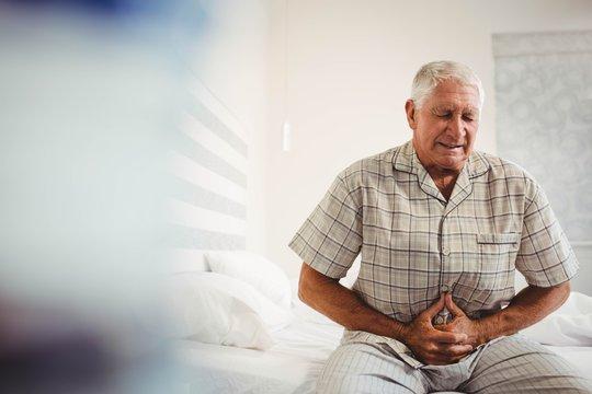 Sick senior man holding stomach