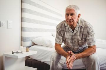 Senior man sitting on bed