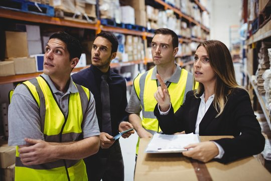 Warehouse manager and workers talking