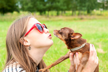 Unconditional love. Teenage girl kissing her brown toy-terrier d