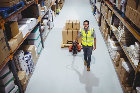 Worker pulling trolley with boxes