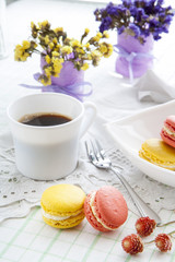 Colorful french macaroons and white coffee cup with soft vintage color