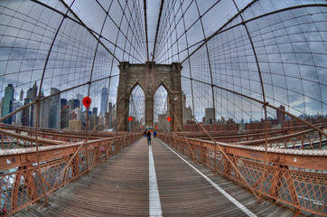 Brooklyn bridge and downtown Manhattan, New York city in the background from a fish eye perspective. HDR image on a cloudy day