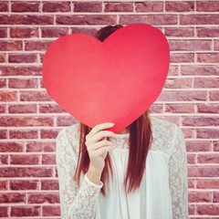 Composite image of smiling hipster woman behind a big red heart
