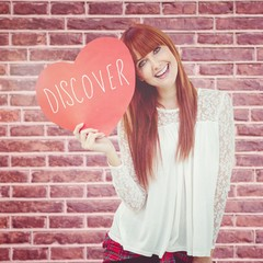 Composite image of smiling hipster woman with a big red heart