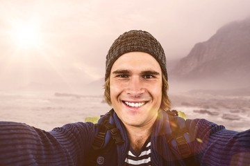Composite image of smiling backpacker hipster holding the camera