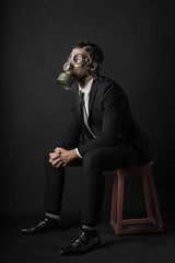Bearded man dressed with a suit wtih a mask gas