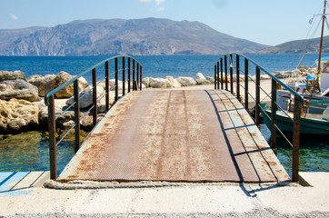 old bridge with rusty metal rails near sea port.Skyros island,Greece