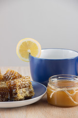 Pieces of golden honey comb on a table with tea, lemon and cinna