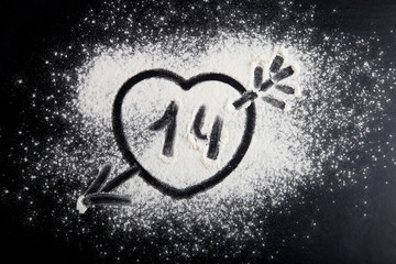 Shape of heart drawn on the flour on a black background