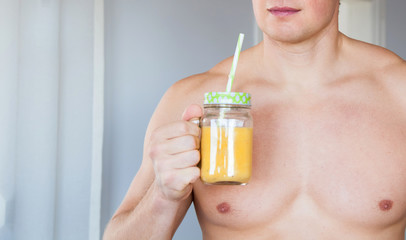 Handsome athletic man drinking organic healthy smoothie.