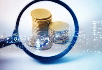 Double exposure of city and the magnifying glass focus at rows of coins for finance and banking concept