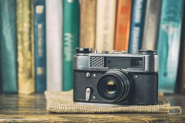 Vintage camera on a shelf with books