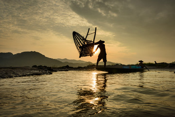 fisherman throwing nets during on sunset in Meakhong river Thai-Loas