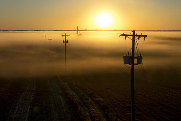 Telephone poles and farm ranch rural countryside silo on a foggy misty morning at sunrise or sunset