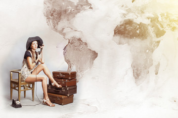 Traveler woman sitting  and dreaming about adventures. Map of the world. Concept of travel