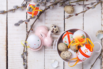 Easter eggs in bucket, decorative rabbit  and willow  branches o