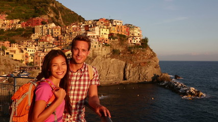 Wall Mural - Hiking couple portrait looking at camera at sunset on holidays travel. Young backpacking Asian woman and Caucasian man enjoying ocean view on vacation in Manarola, Cinque Terre, Liguria, Italy