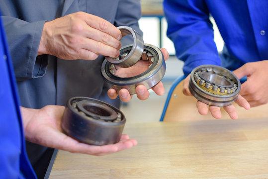 Three men holding bearings