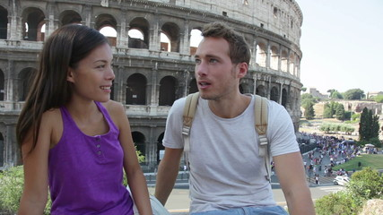 Aufkleber - Couple in Rome by Colosseum talking in Italy. Happy young friends traveling and sightseeing having fun in front of Coliseum. Love and travel concept with multiracial couple.