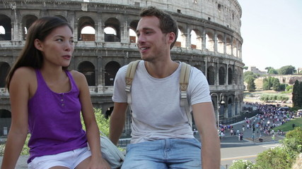 Aufkleber - Couple in Rome by Colosseum talking in Italy. Happy lovers on honeymoon sightseeing having fun in front of Coliseum. Love and travel concept with multiracial couple.