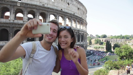 Aufkleber - Happy travel couple taking selfie by Coliseum, Rome, Italy. Smiling young romantic couple traveling in Europe taking self portrait photo with smartphone camera in front of Colosseum. Man and woman.