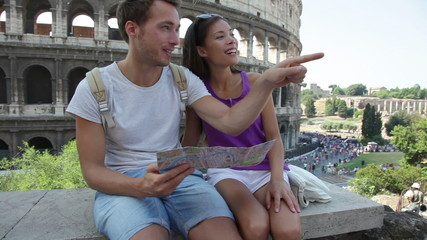 Aufkleber - Tourists holding map by Colosseum sightseeing on travel vacation in Rome, Italy. Happy tourist couple, man and woman traveling on holidays in Europe smiling happy. Interracial Asian Caucasian couple