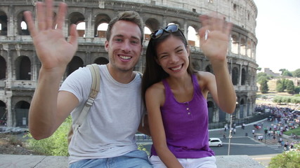 Aufkleber - Travel couple waving hello hands by Colosseum, Rome, Italy. Smiling young romantic couple traveling in Europe looking at camera smiling in front of Coliseum. Caucasian man and Asian woman.