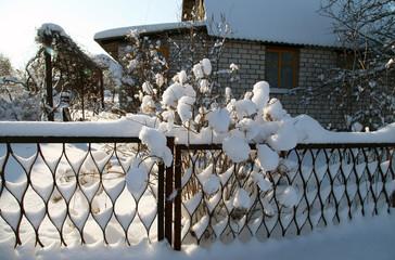 дачный забор под большим снежным покровом