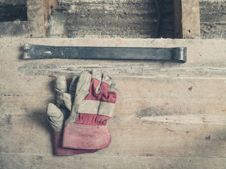 Gloves and crowbar on wooden floor