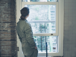 Woman in boiler suit looking out the window