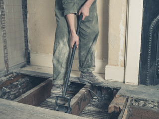 Young woman in boiler suit removing floor boards