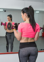 Young woman working out biceps in the gym