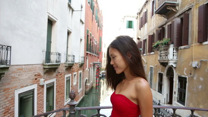 Wall Mural - Happy beautiful woman in red summer dress walking over canal bridge smiling in Venice, Italy. Pretty sexy fashion model girl in her 20s. Mixed race Asian Caucasian female model outside.
