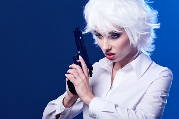 beautiful sexy girl holding gun . blue background