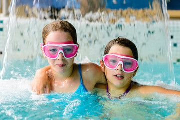 Cute happy girls in pink goggles mask in the swimming pool
