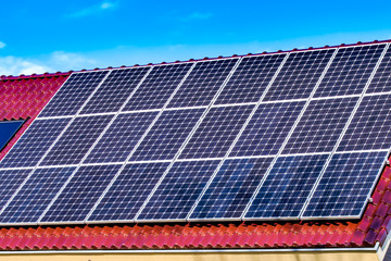 Green Solar panels producing electricity / Green Solar panels on the roof of a house facing the sun producing green electricity