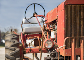 Old vintage antique red farm working tractor outside in the sun on a clear day