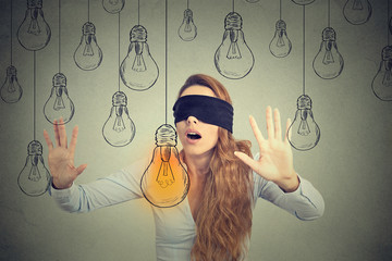 Blindfolded young woman walking through light bulbs searching for bright idea