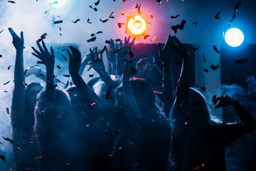 party at a nightclub, young people boys and girls dancing in smoke and confetti
