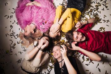 Cheerful friends lying on the floor in nightclub