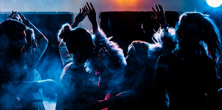 party at a nightclub, young people boys and girls dancing in a smoke