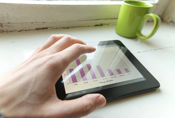 black tablet with blank screen in the hands on table