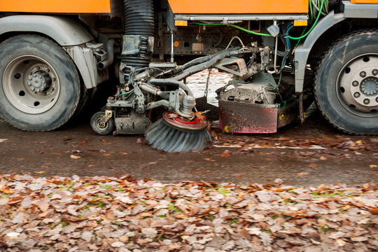 Orange street sweeper machine cleaning the street from fall foliage