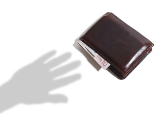 Shadow of Hand Reaching for a Leather Wallet with Euro Currency