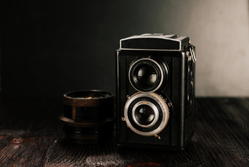 The old Soviet film camera and the lens on the old wooden table. Stylized images.
