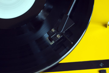 Turntable in yellow case with black tonearm playing a vinyl record with white label. Horizontal photo top view closeup