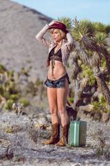 woman traveler walking with suitcase in desert