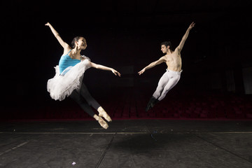 Two ballet dancers jumping.