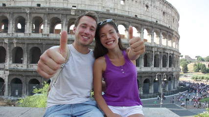 Aufkleber - Travel couple happy thumbs up by Colosseum, Rome, Italy. Smiling young romantic couple traveling in Europe looking at camera smiling in front of Coliseum. Caucasian man and Asian woman.